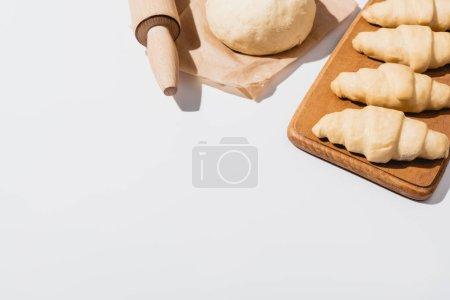 frische Croissants auf Holzschneidebrett in der Nähe von rohem Teig, Nudelholz auf weißem Hintergrund