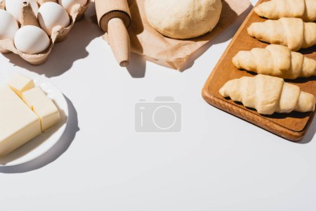 Photo for Fresh croissants on wooden cutting board near raw dough, rolling pin, butter and eggs on white background - Royalty Free Image