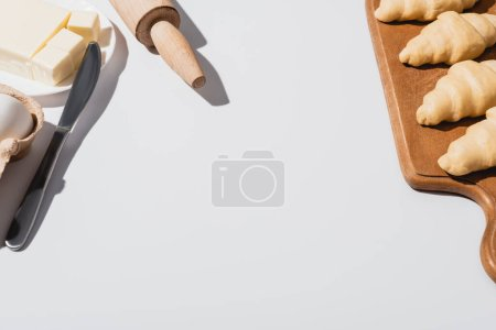 fresh croissants on wooden cutting board near knife, rolling pin, butter on white background