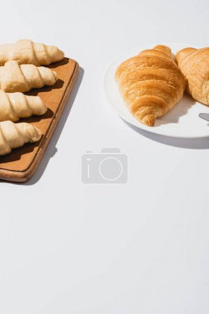 Photo for Fresh baked and raw croissants on white background - Royalty Free Image