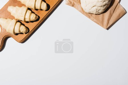 top view of fresh croissants on wooden cutting board near raw dough on white background
