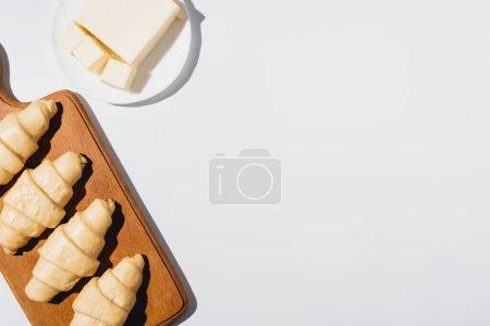 Photo pour Vue de dessus des croissants crus frais sur planche à découper en bois près du beurre sur fond blanc - image libre de droit