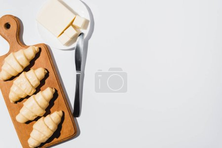 Photo for Top view of fresh raw croissants on wooden cutting board near butter on plate with knife on white background - Royalty Free Image