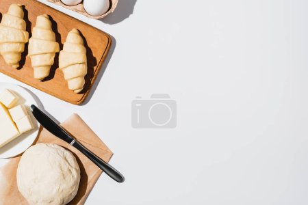 Photo for Top view of fresh croissants on wooden cutting board near raw dough, knife, butter and eggs on white background - Royalty Free Image