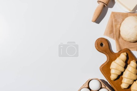 Photo for Top view of fresh croissants on wooden cutting board near raw dough, rolling pin, butter and eggs on white background - Royalty Free Image