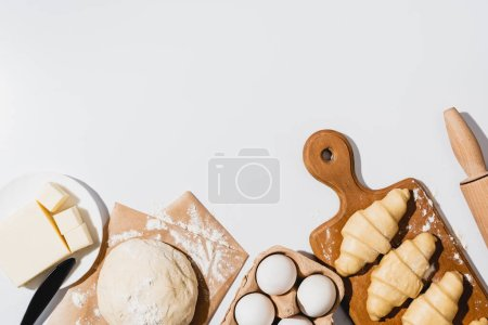Photo for Top view of fresh croissants on wooden cutting board near raw dough, knife, rolling pin, butter and eggs on white background - Royalty Free Image