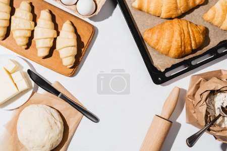 Photo for Top view of raw and baked croissants on baking tray near ingredients on white background - Royalty Free Image