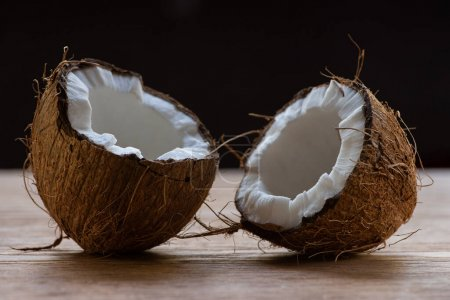 Photo for Fresh tasty coconut halves on wooden table isolated on black - Royalty Free Image