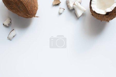 Photo pour Vue de dessus de la moitié de noix de coco entière et fissurée savoureuse et des morceaux sur fond blanc - image libre de droit
