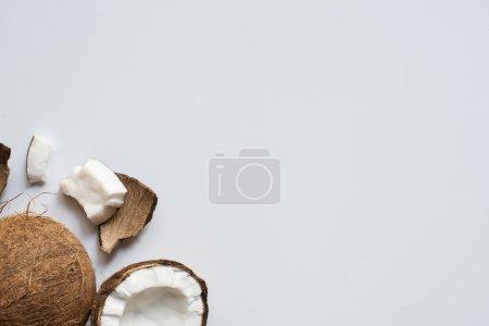 Photo pour Vue de dessus de noix de coco fraîches savoureuses entières et craquelées sur fond blanc - image libre de droit