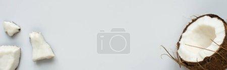 Photo pour Vue de dessus de noix de coco fraîche savoureuse moitié et des morceaux fissurés sur fond blanc, vue panoramique - image libre de droit