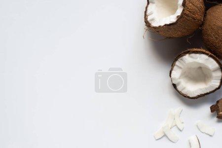 Photo pour Vue de dessus de moitiés de noix de coco fraîches et de flocons sur fond blanc - image libre de droit