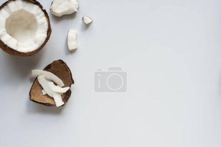 Photo pour Vue de dessus de fraîche savoureuse moitié de noix de coco craquelée avec des flocons et coquille sur fond blanc - image libre de droit
