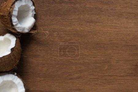Photo pour Top vue de noix de coco fraîches et craquées sur une table en bois - image libre de droit