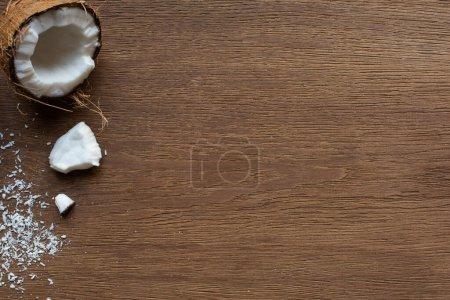 Photo pour Fraîches savoureuses noix de coco entières et craquelées et flocons sur table en bois - image libre de droit