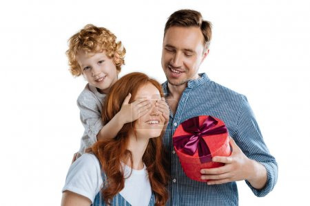 Man and son presenting gift to woman