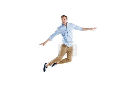 Photo for Young casual man jumping with arms outstretched isolated on white - Royalty Free Image