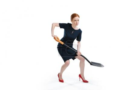 Photo for Red hair businesswoman digging with shovel and looking at camera isolated on white - Royalty Free Image