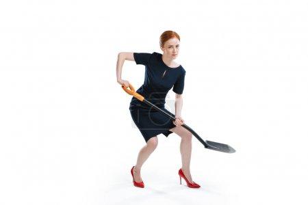 Photo pour Femme d'affaires cheveux roux creuser avec la pelle et en regardant la caméra isolée sur blanc - image libre de droit