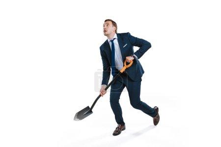 Businessman in formal wear digging with shovel