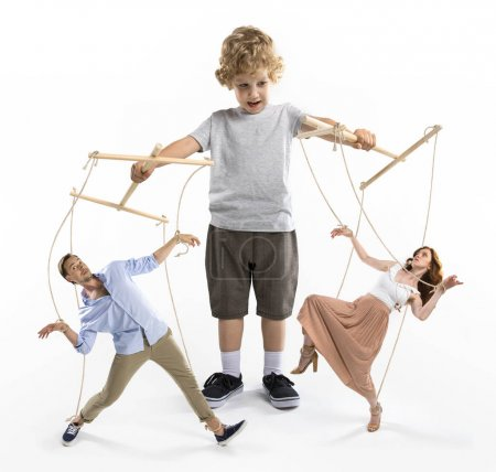 Little boy puppeteer controlling parents with stri...