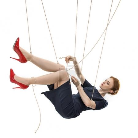 Photo for Businesswoman trying to break free while hanging on manipulating ropes isolated on white - Royalty Free Image