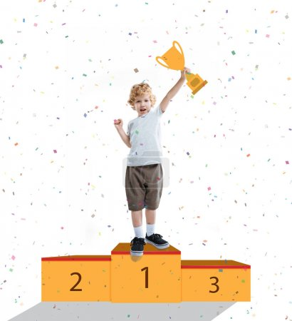 Photo for Little kid boy showing gesture of success and holding goblet, standing on pedestal - Royalty Free Image