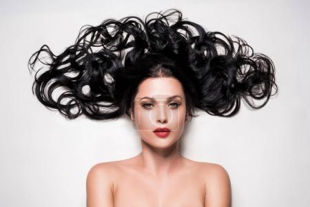 Photo pour Jeune femme avec de beaux cheveux bouclés composés isolés sur blanc - image libre de droit