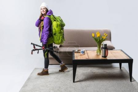 beautiful sportswoman in warm clothing with backpack and hiking equipment ready to travel