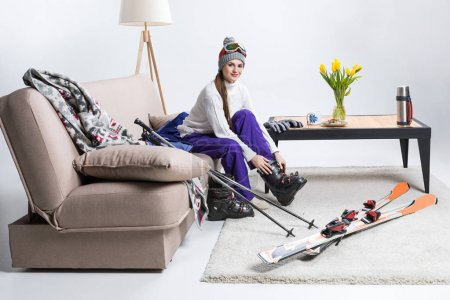 young female skier wearing ski boots while sitting on sofa at home