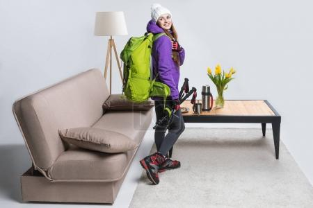 young girl in warm clothing with backpack and hiking equipment ready to travel
