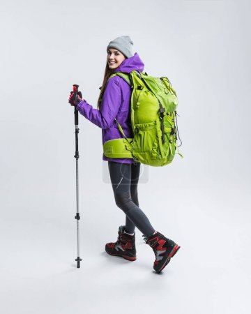 female hiker in warm clothing with backpack and hiking equipment, isolated on grey