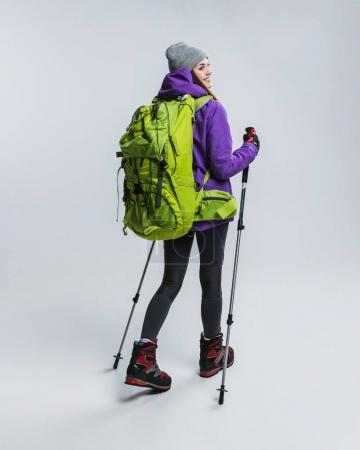 beautiful hiker with backpack and hiking sticks, isolated on grey