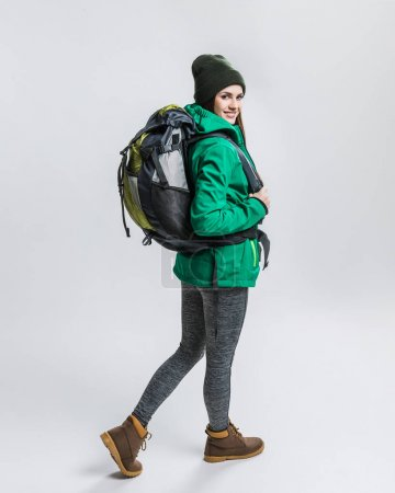 Photo for Smiling female traveler with backpack, isolated on grey - Royalty Free Image