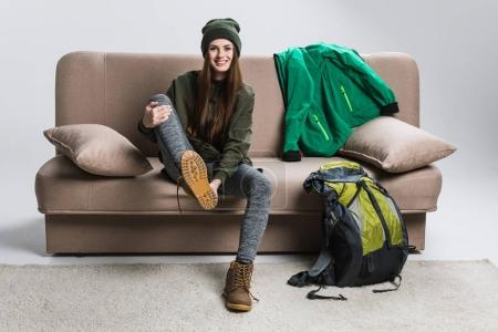 beautiful traveler wearing hiking boots and warm clothing on sofa
