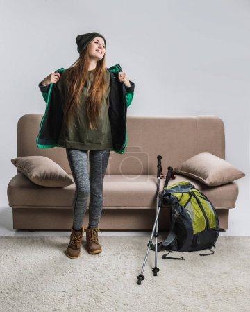happy woman in warm clothing with backpack and hiking equipment at sofa