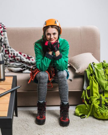 beautiful climber in helmet with backpack and climbing equipment sitting on sofa