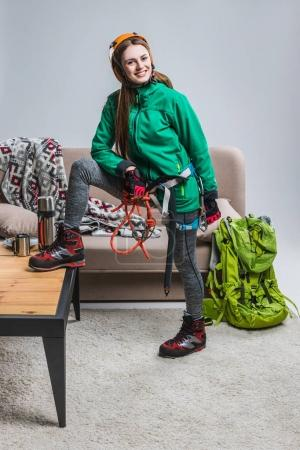 Photo for Beautiful smiling climber in helmet with climbing equipment at home - Royalty Free Image