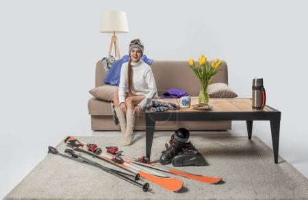 beautiful young sportswoman wearing warm socks, ski equipment near