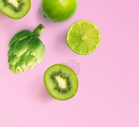Photo for Composition of freshly cut kiwis, lime and artichoke laid out on a pink background - Royalty Free Image