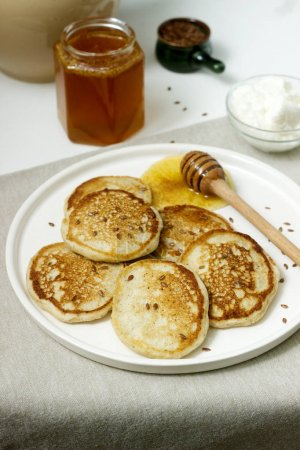 Linen pancakes served with honey and cream cheese on a light background. Rustic style.