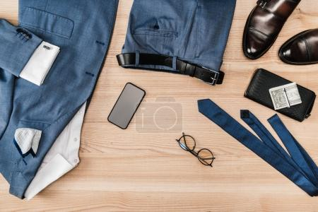 suit and accessories with smartphone on tabletop