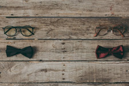 stylish bow ties and eyeglasses on tabletop
