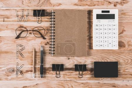 Photo for Top view of calculator with eyeglasses and office supplies on wooden tabletop - Royalty Free Image