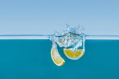 lemon slices falling into water with splashes