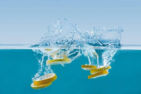Photo for Side view of fresh lemon slices falling into water with splashes - Royalty Free Image