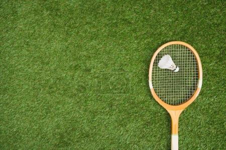 Photo pour Vue du dessus de la raquette de badminton avec volant sur terrain gazonné - image libre de droit