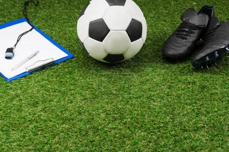 clipboard with soccer ball and boots on grass