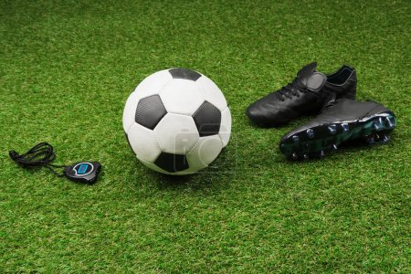 stopwatch with soccer ball and boots on grass