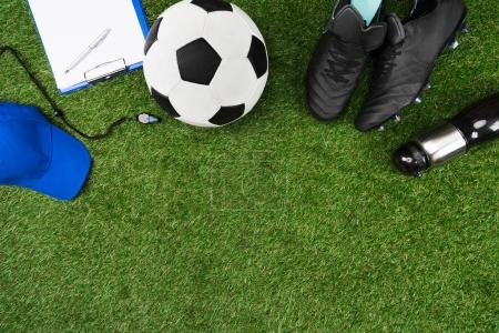 Photo for Top view of clipboard with soccer ball and boots on grass - Royalty Free Image